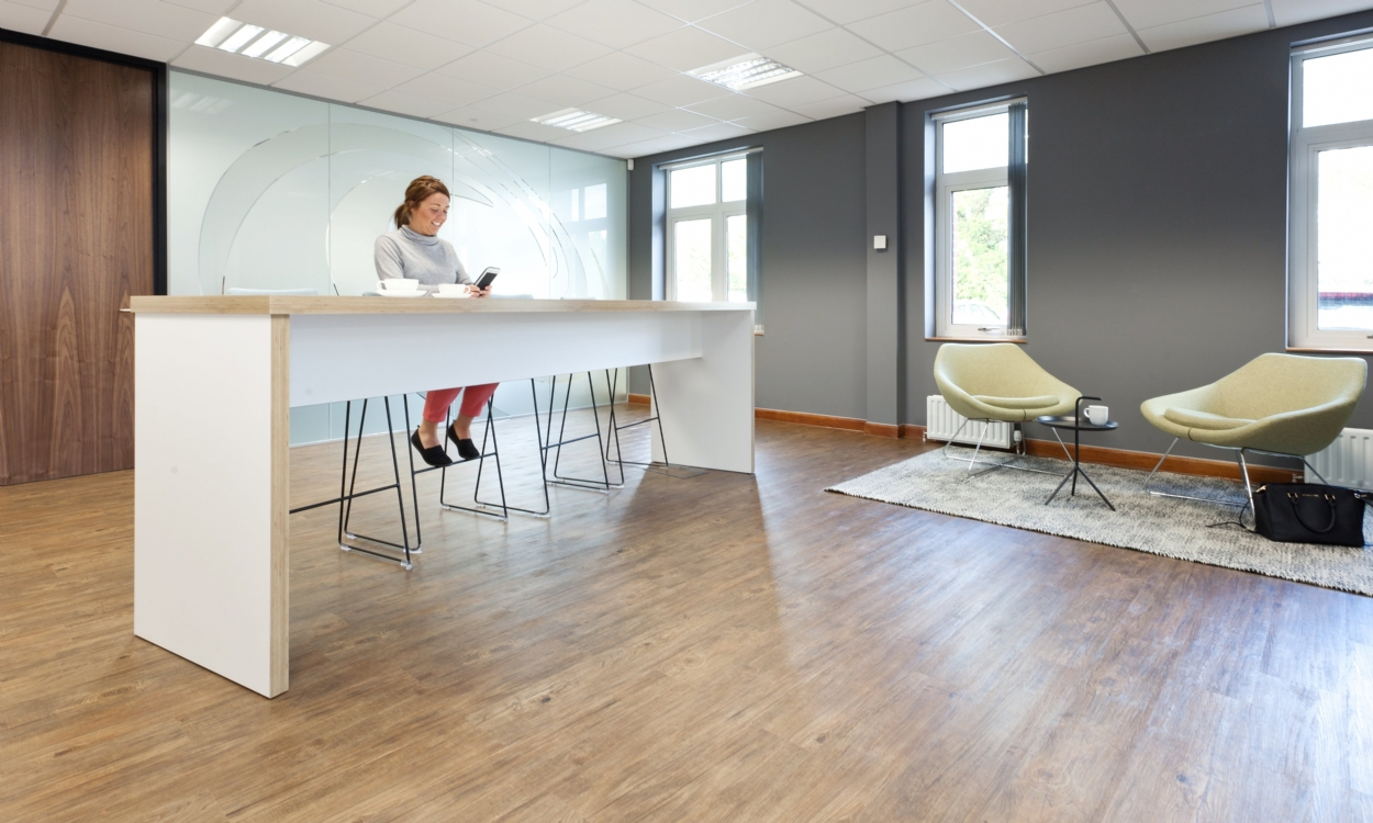 Office worker seated in new fitted office coffee break area