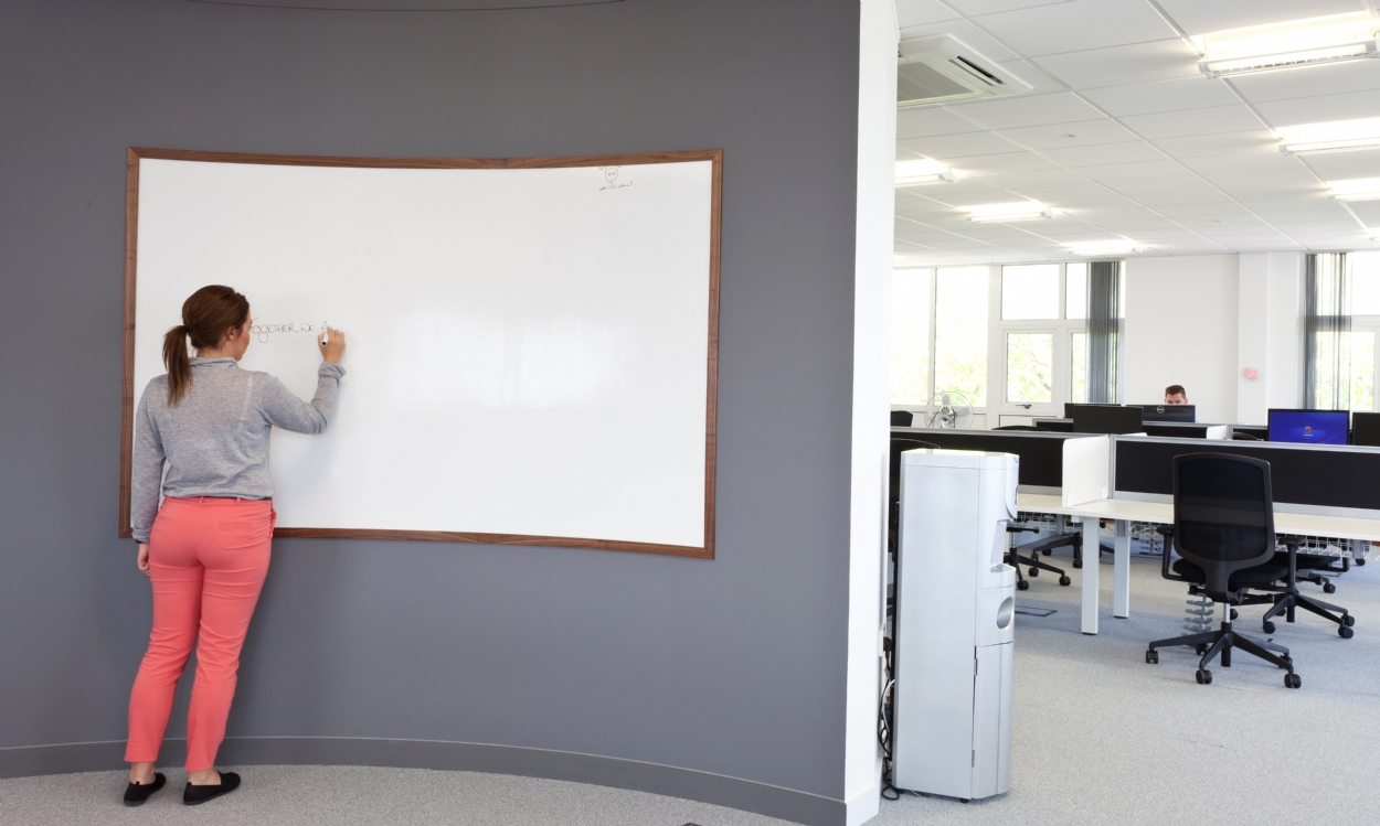 Office worker writing on whiteboard in newly fitted IT office