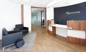 New office reception design showing Procentia company logo behind reception desk and soft office furnishing