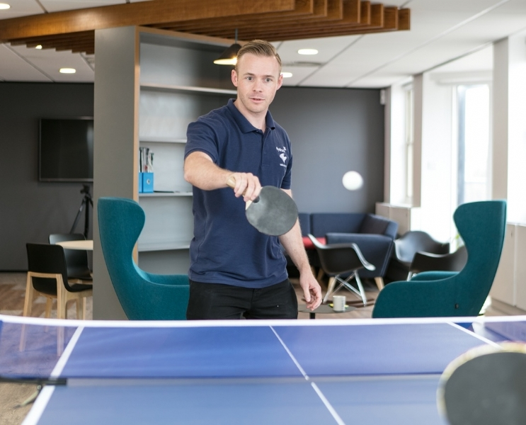 Playing table tennis in new office break room